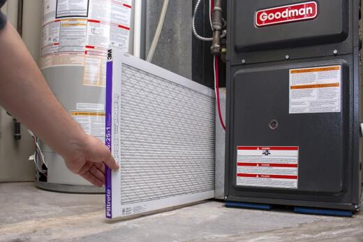 Changing out the air filter on a home furnace.